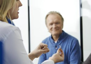 consultant demonstrating a hearing aid