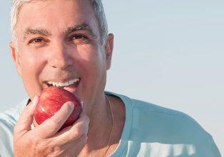 Happy senior eating apple