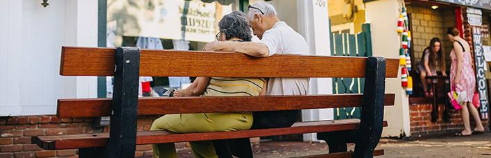 older couple sitting on a bench together