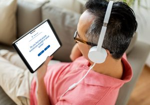 person with headphones looking at tablet
